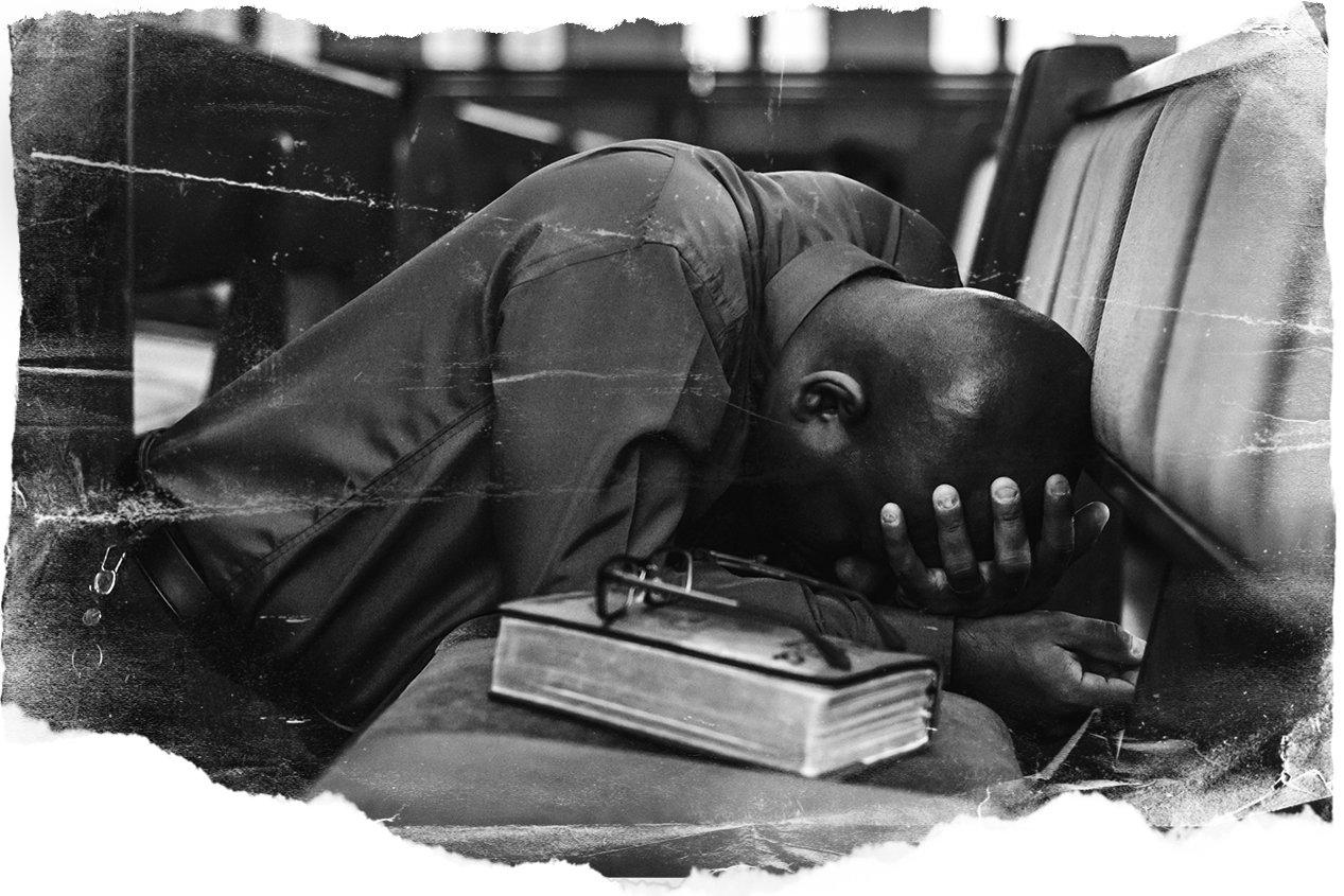 Black man kneeling down for prayer and intercession